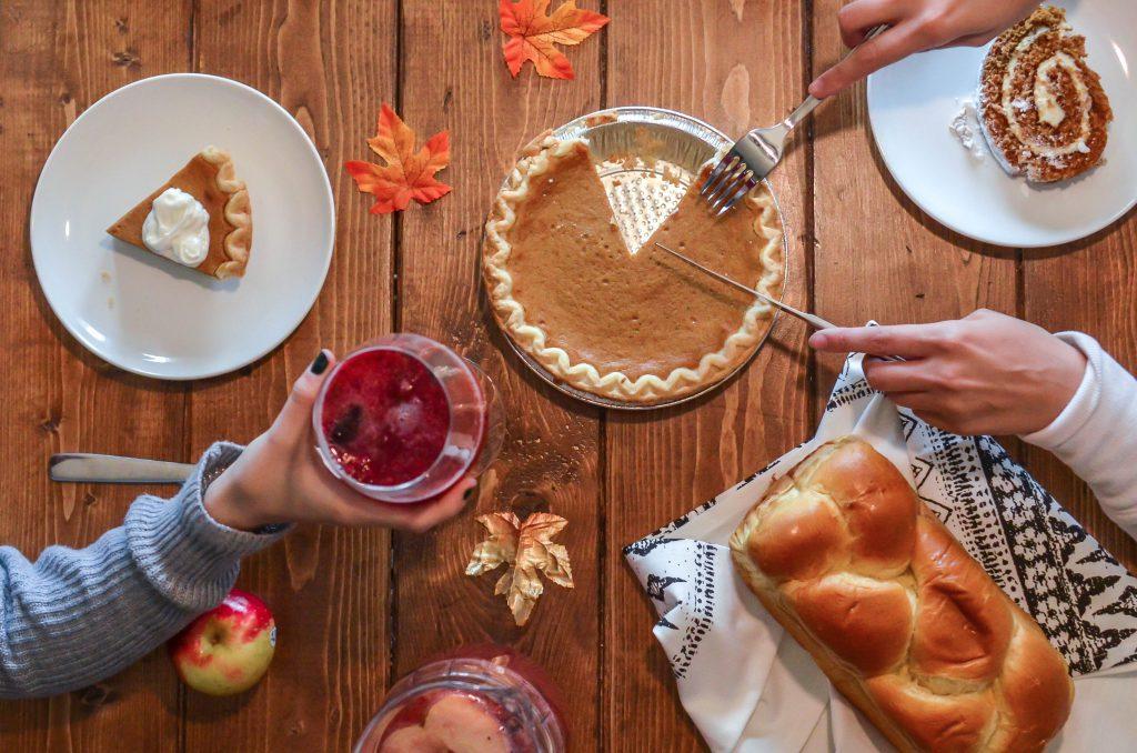 thanksigiving food being shared including pumpkin pie