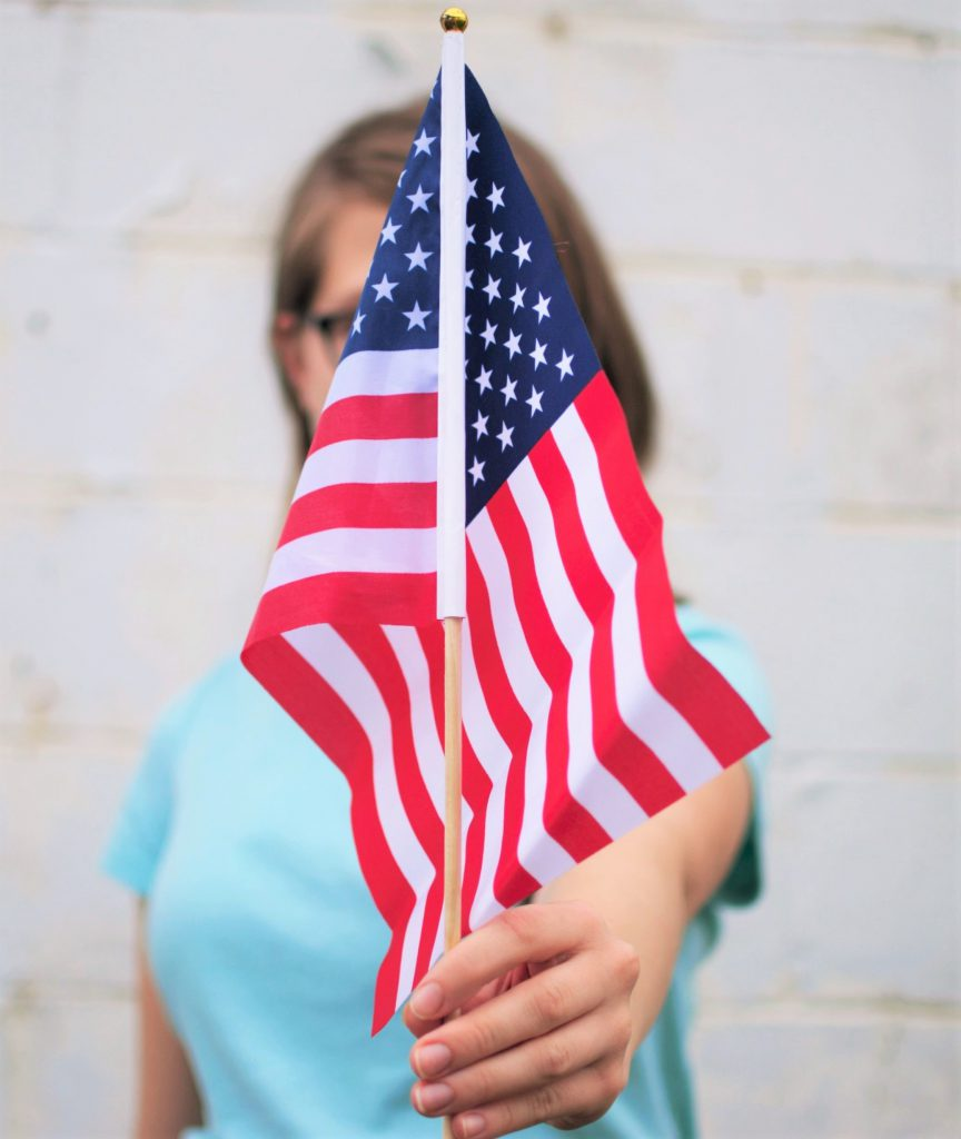 woman in glasses holding out an american flag