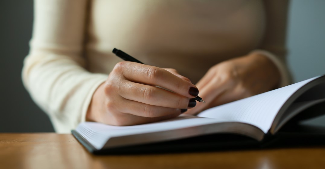 woman writing down her language learning goal for the year in her diary