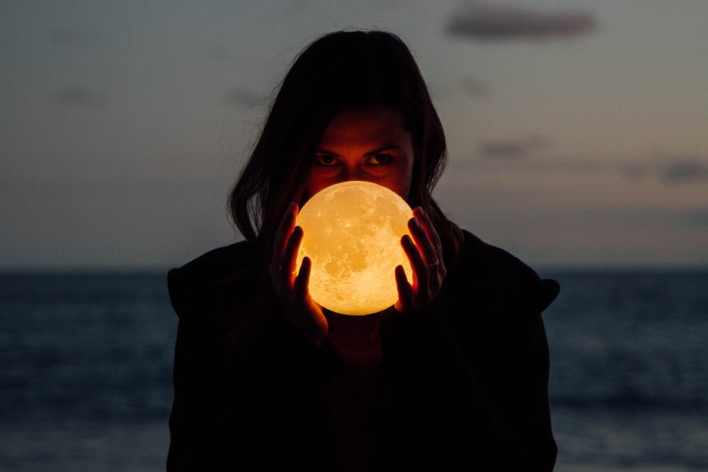 a woman holding the moon in her hands