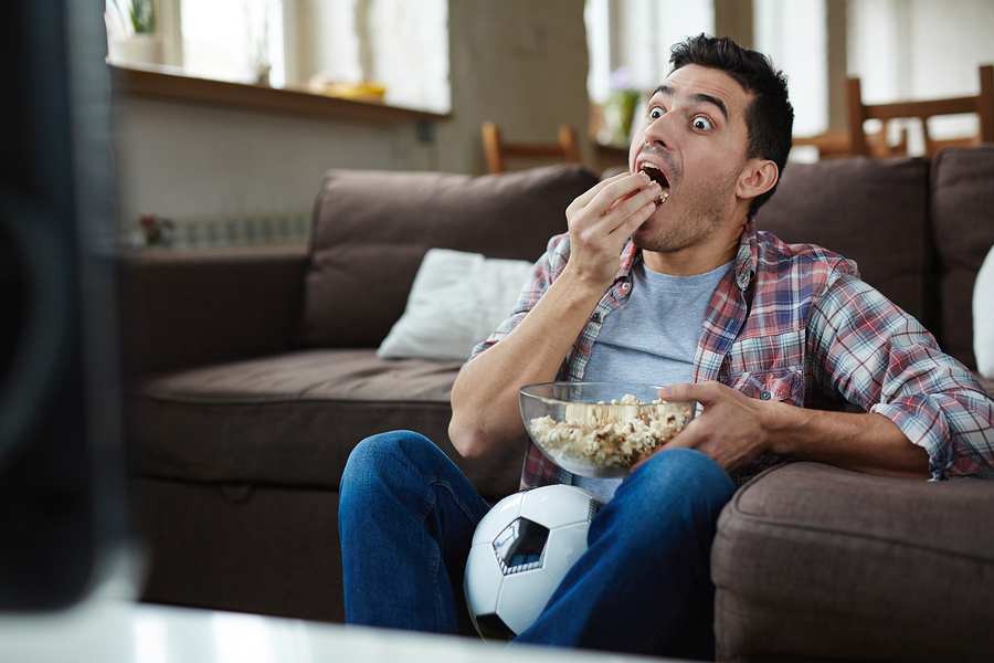 man eating on the sofa and being a typical couch potato