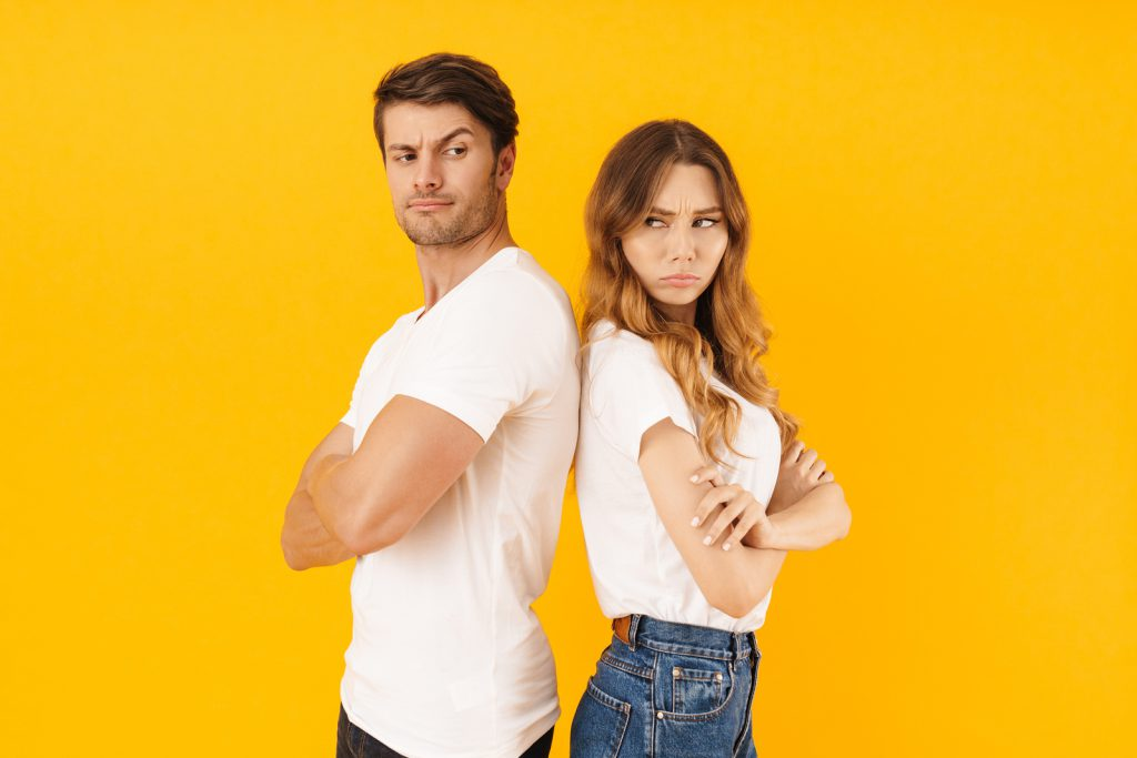 Portrait of serious offended couple man and woman in basic t-shi