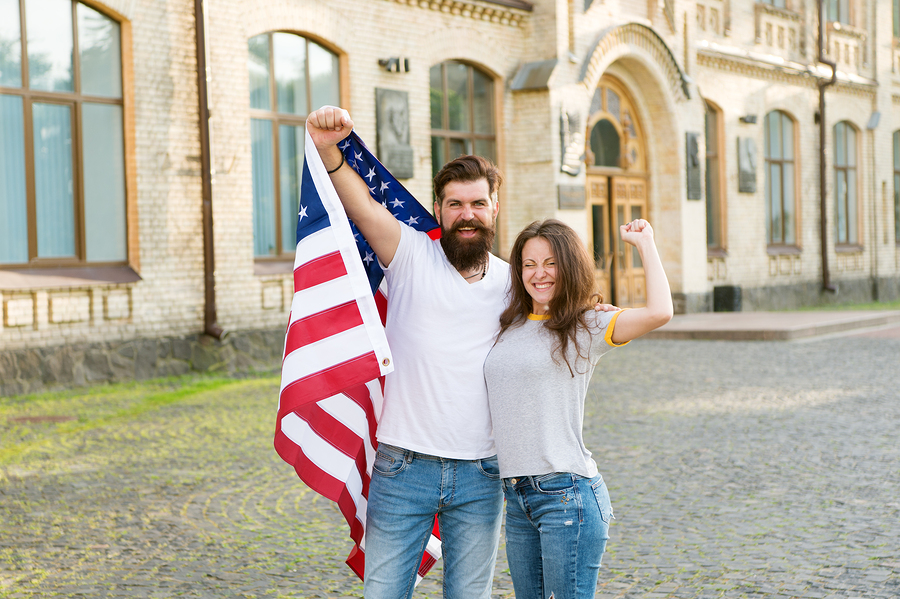 American couple USA flag. Patriotic spirit. Independence day. American tradition. Students exchange program. National holiday. Hipster and girl celebrate 4th of July. American patriotic people.