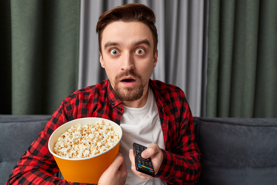 Attractive bearded guy with bucket of fresh popcorn and remote control looking at camera with astonished film expression while watching horror film at home
