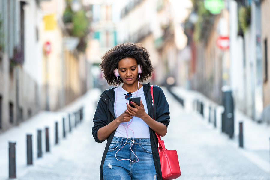 Beautiful Afro American Girl Listening Music on Headphones Outdoors. Latin American Woman Using Pink Headphones and Having Fun in the Street. Lifestyle Concept.