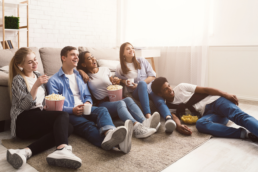 Happy friends watching movie, sitting on floor at home