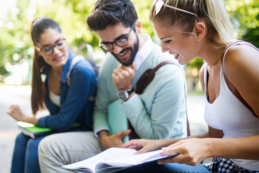 Happy young university students studying together. Group of multiracial friends in college