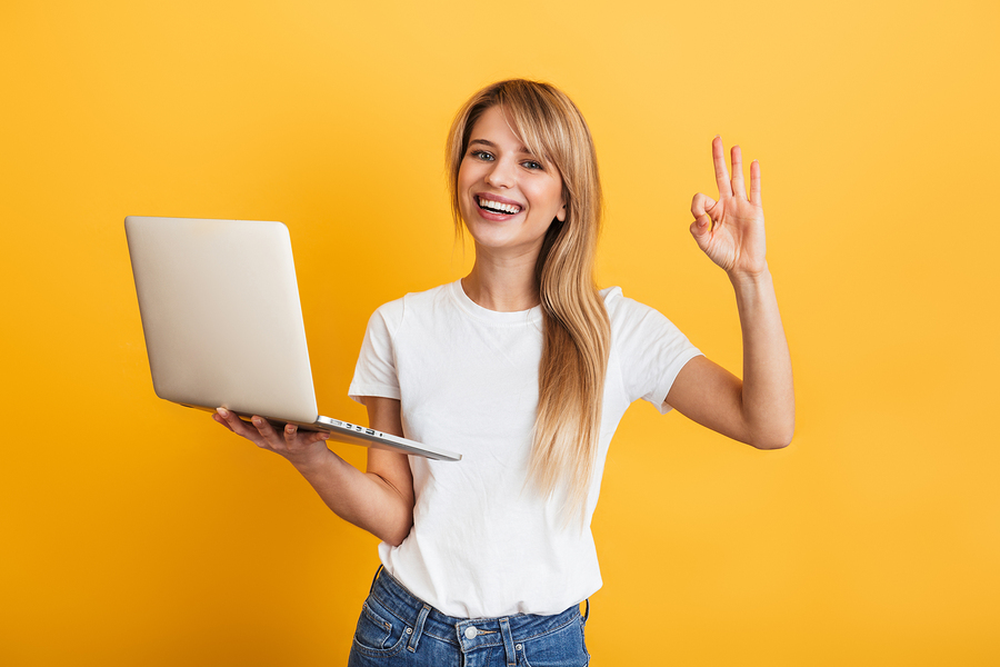 blonde woman holding a laptop being very happy after recently completing the lingoda language sprint