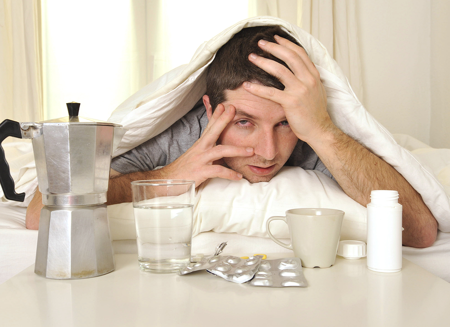 exhausted young Man in bed with coffee water and tablets suffering hangover and headache