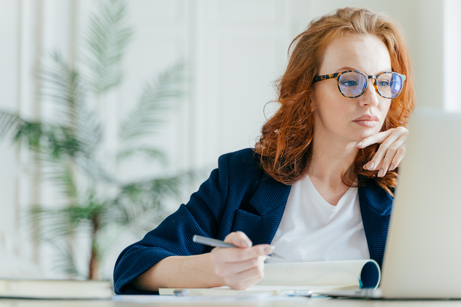 serious-female-writing-using-laptop