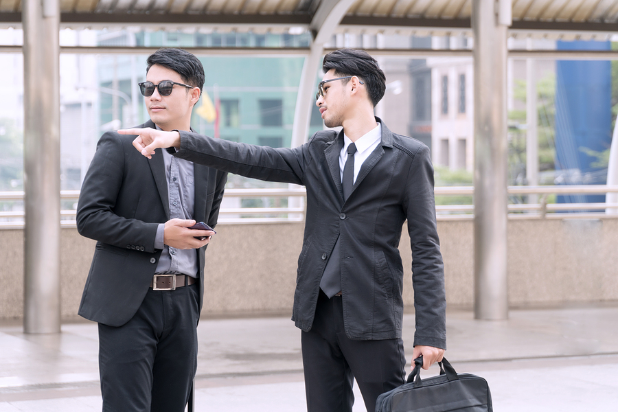 Young businessmen pointing the way to stranger man who was meet on the street. Young businessman wearing a suit and sunglasses with bag drag ask for directions from strangers. lifestyle concept.
