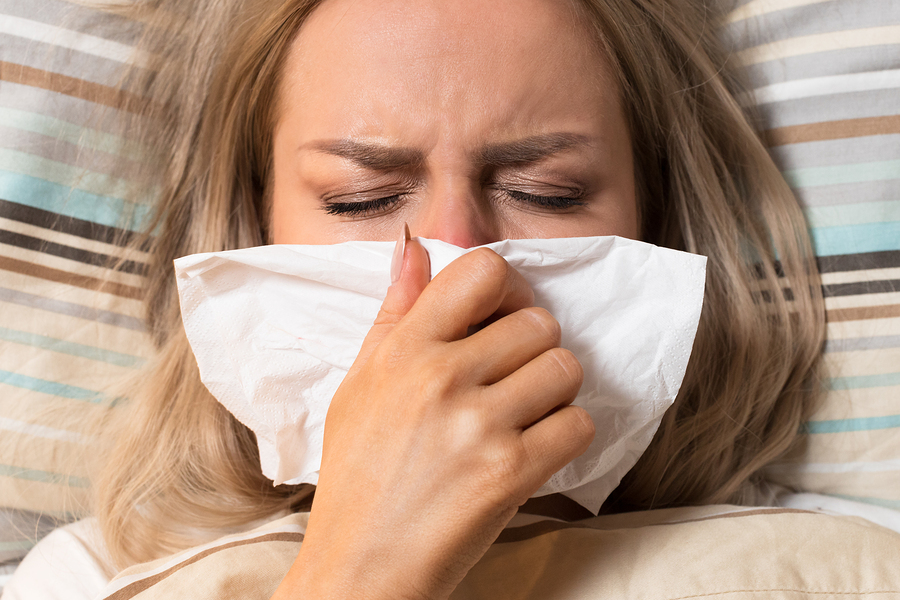 Young European upset and sick woman with paper napkin blowing nose, lies on the pillow under the blanket, closed eyes/ Sick desperate female has flu/ Rhinitis, cold, sickness, allergy concept