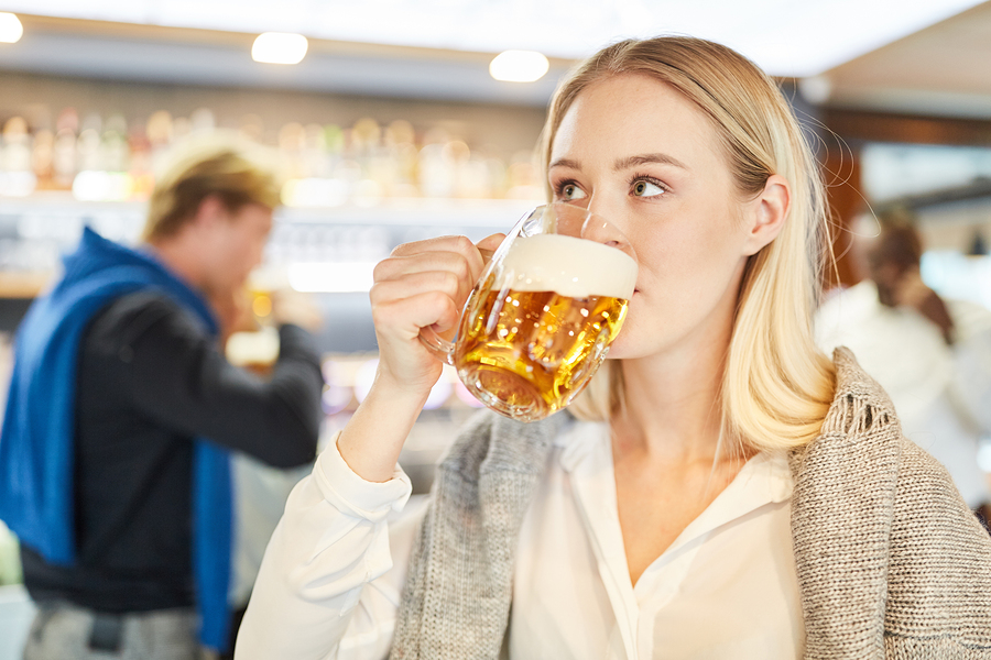 Young woman drinking beer at the end of work in a pub or pub