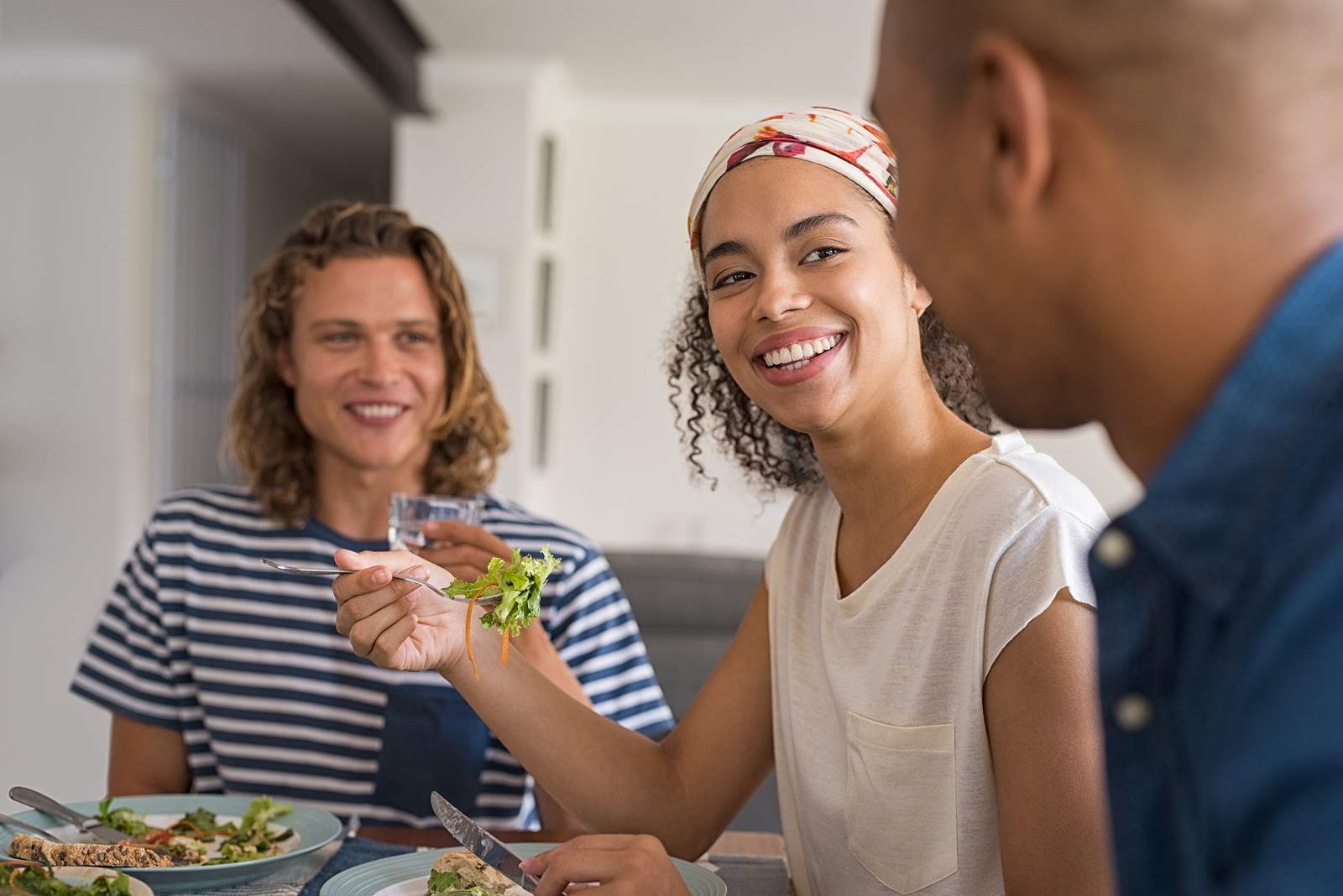 Beautiful african woman eating fresh salad with friends for lunch. Happy cheerful friends in a conversation during lunch at home. Young friends meeting each other for healthy meal.
