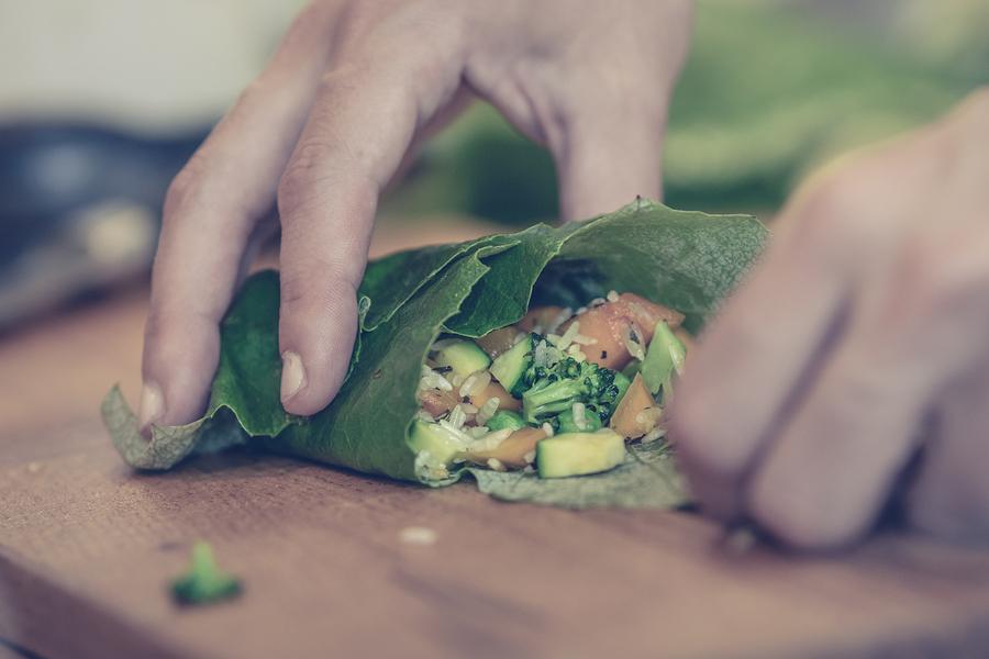 Close up of hands making vegetarian rolls food. Healthy food. Vegetarian food. Nutritious food. Female hands making vegetarian rolls. Food. Vegetarian rolls. Making food. Healthy food lifestyle.