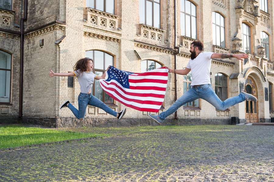 Explore USA. Vacation and travel. Independence day. National holiday. Bearded hipster and girl jumping. 4th of July. American tradition. American patriotic people. American couple USA flag outdoors.