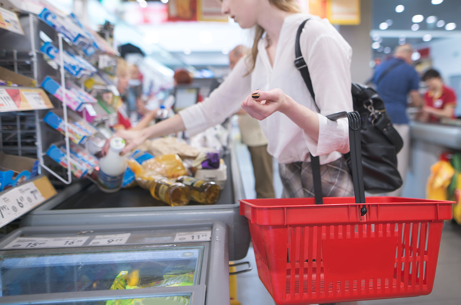 Girl with red basket standing at the checkout in the supermarket. Focus on shopping cart. Payment products in the store at the checkout. Amount pays for purchases at the supermarket's cash desk. Cashier is passive-aggressive.
