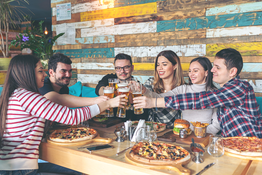 Happy young hipster friends celebrating by toasting with beer eating pizza and burgers at bar restaurant - Friendship concept with young people enjoying time together and having genuine fun at rustic pizzeria - cheers