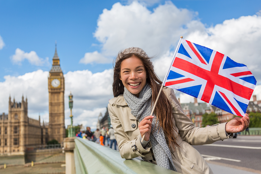London Big Ben Westminster travel tourist woman showing United Kingdom UK flag. Europe vacation destination Asian girl holding Great Britain british flag Union Jack sign.