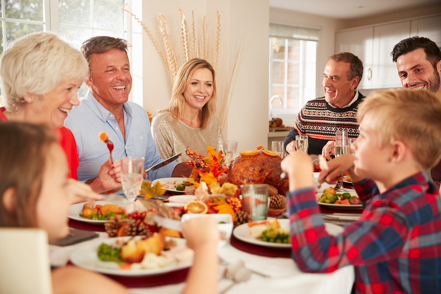 Multi-Generation Family Sitting At Table Making A Toast Whilst Eating Thanksgiving Meal At Home Together