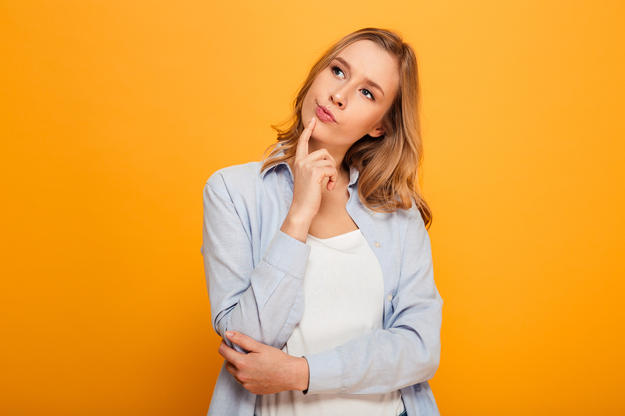 Portrait of lovely woman with auburn hair looking aside being deep in thoughts and doing pensive gesture isolated over yellow background