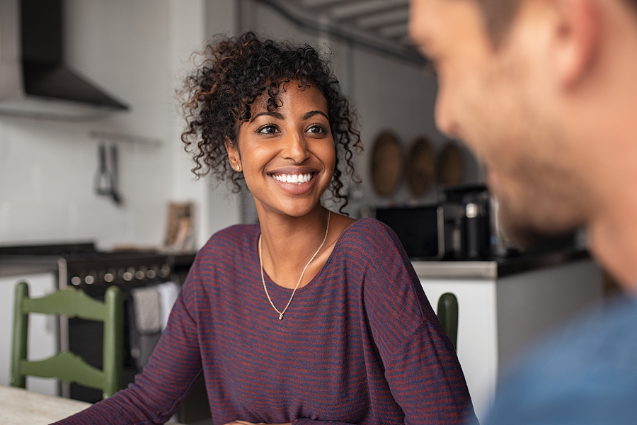 Smiling african american woman with man at home in conversation. Beautiful young loving wife talking to husband in living room. Portrait of happy black girl sitting at table and talking with guy.