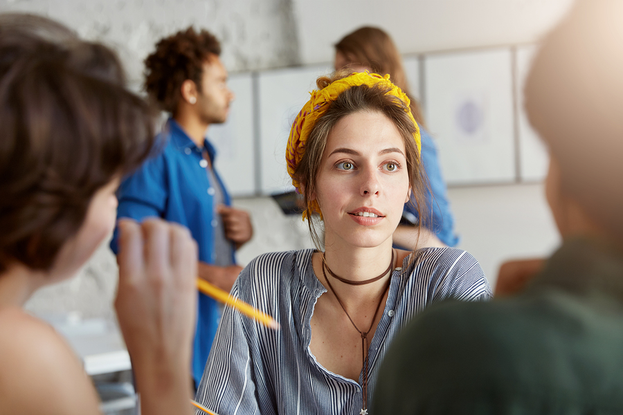 Stylish young female teacher having attentive look during English lesson at cafe listening to her unrecognizable students seated with their backs to camera. People modern lifestyle and communication