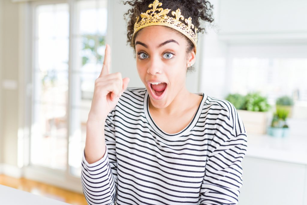 Young african american girl wearing golden queen crown on head pointing finger up with successful idea