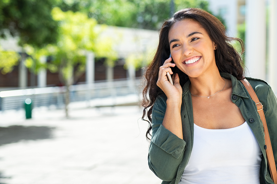 Young latin woman talking on mobile phone and looking away. Successful girl in casual calling on smartphone in city while standing on sidewalk. Beautiful hispanic woman talking on phone while walking
