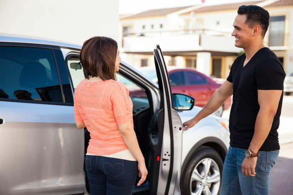Young Hispanic man being a gentleman and opening the car door for her date