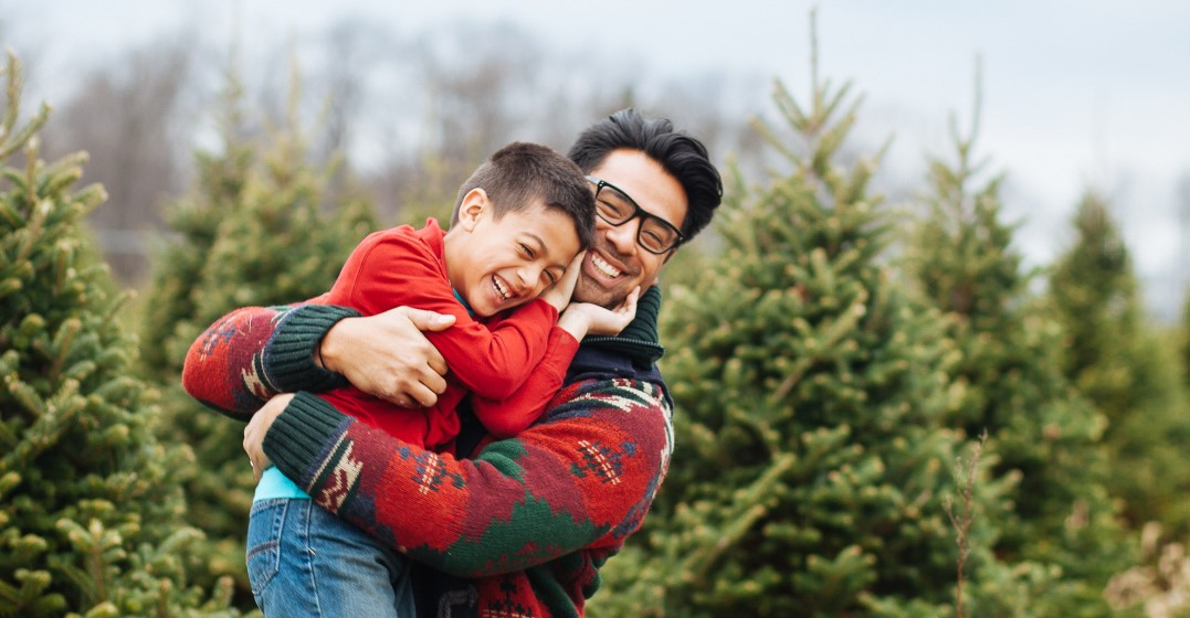 man and his child celebrating merry christmas with christmas trees
