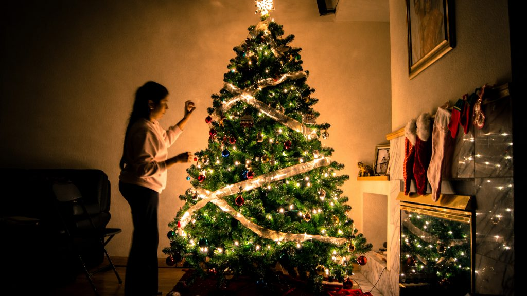 woman decorating a christmas tree feeling festive and merry