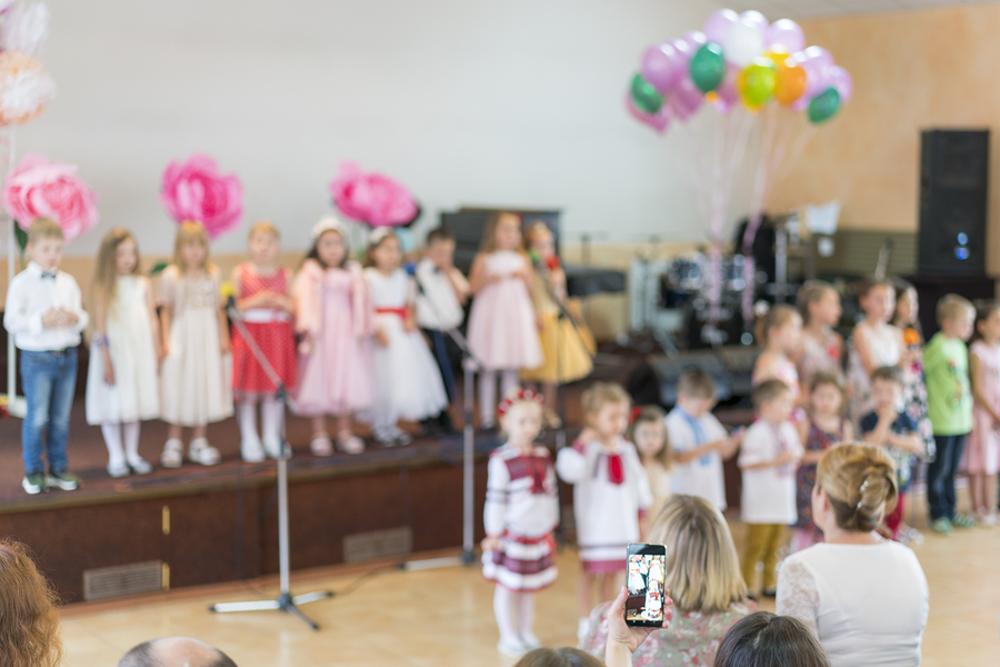 Childrens party in primary school. Young children on stage in kindergarten appear in front parents. blurry. back to school