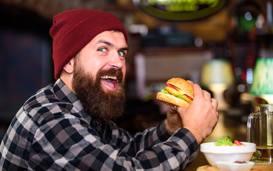 Hipster hungry man eat burger. Man with beard eat burger menu. Brutal hipster bearded man sit at bar counter. High calorie food. Cheat meal. Delicious burger concept. Enjoy taste of fresh burger