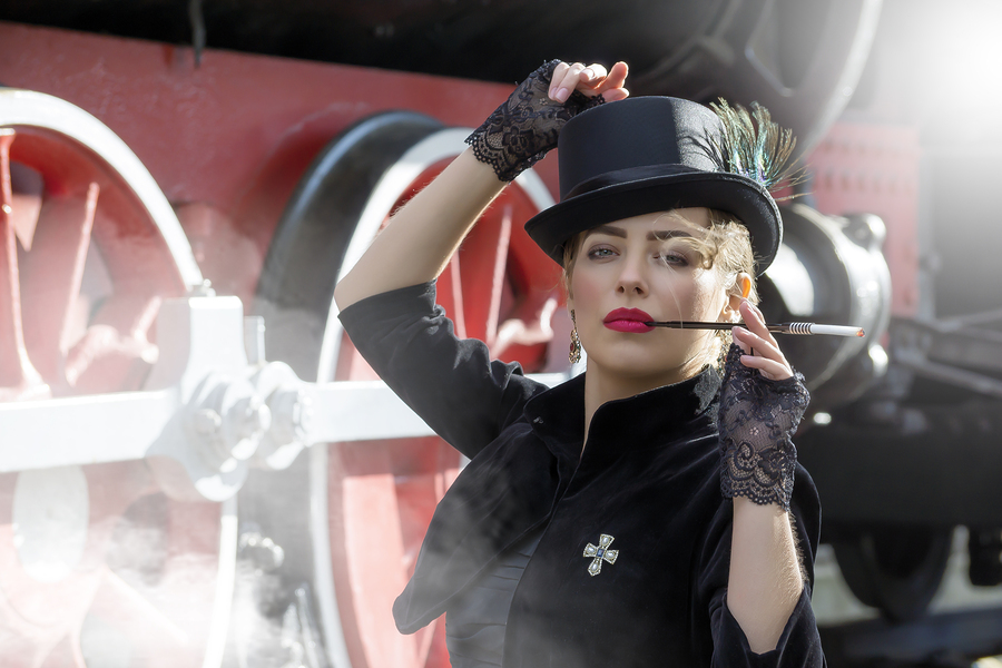 Portrait of a beautiful girl in a hat and a cigarette near an old steam train in a steampunk style.