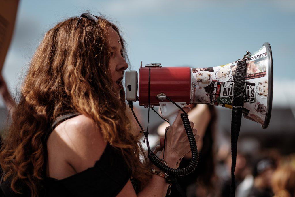woman speaking confidently through megaphone