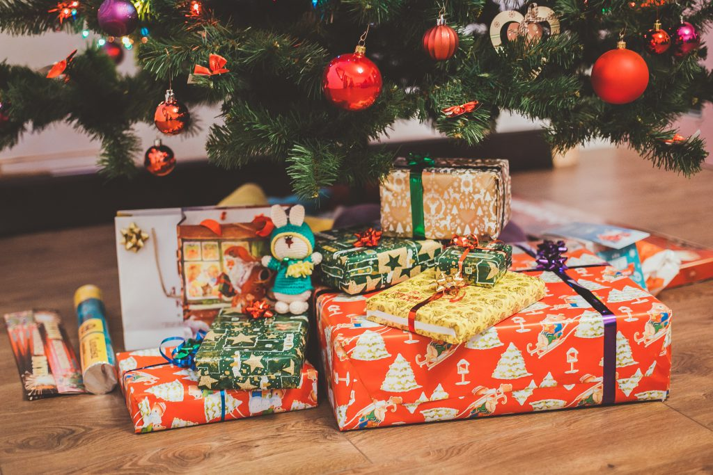 chritmas presents under the christmas tree wrapped in colourful wrapping paper