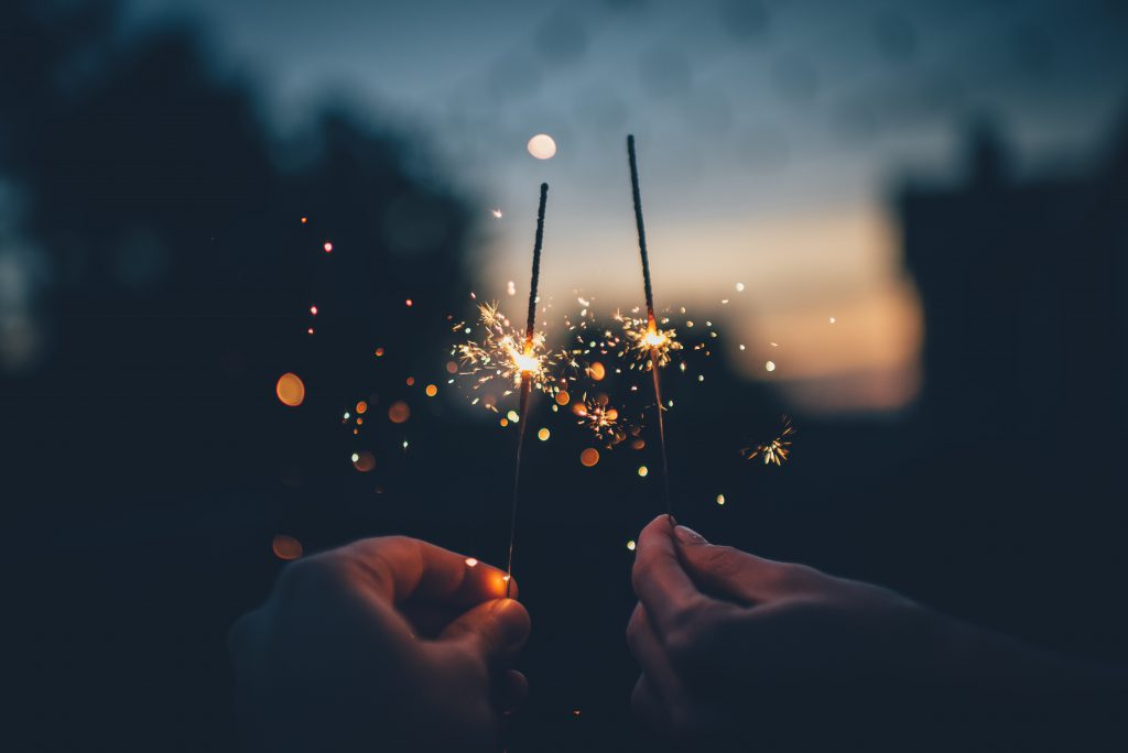 two people lighting sparklers to celebrate new years eve