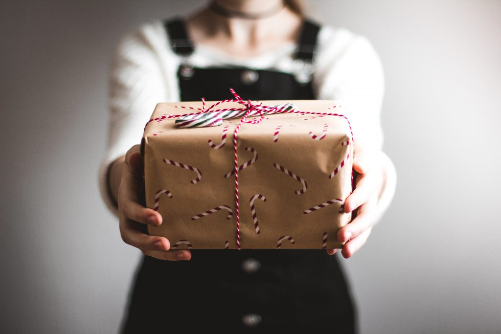woman holding a christmas present wapped in candy cane wrapping paper and merry christmas