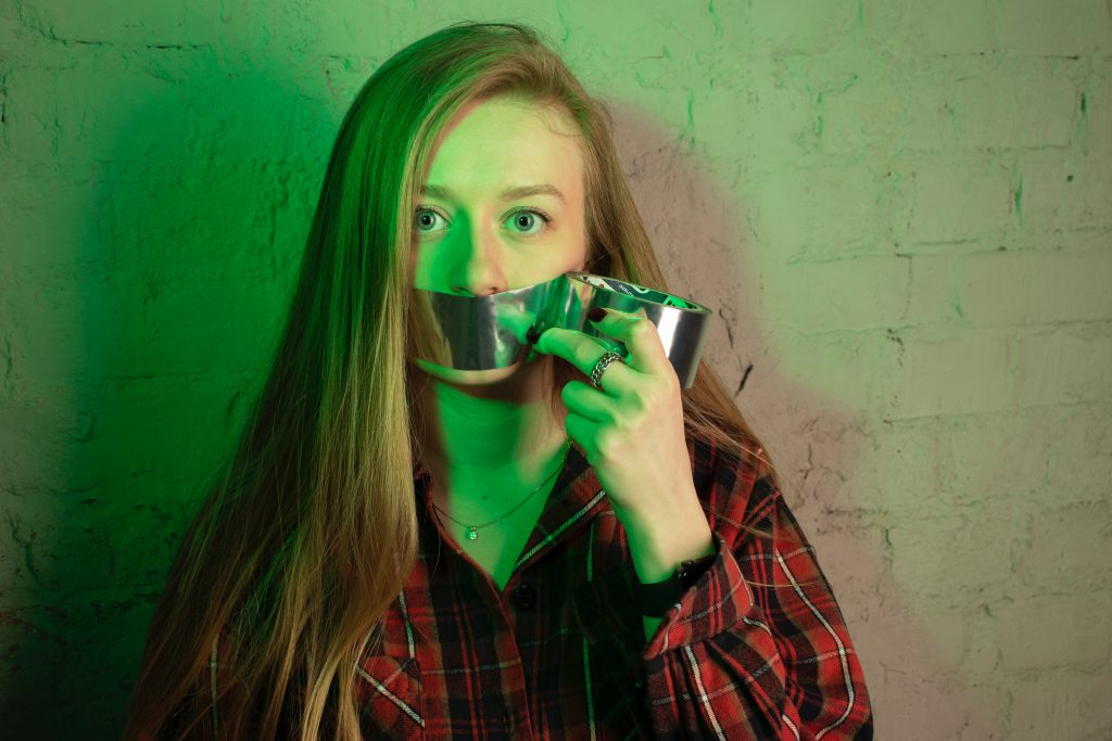 woman with tape over her mouth who is struggling to speak her new language
