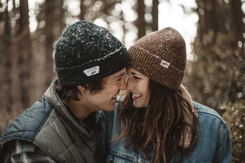 couple cuddling at christmas time wearing hats