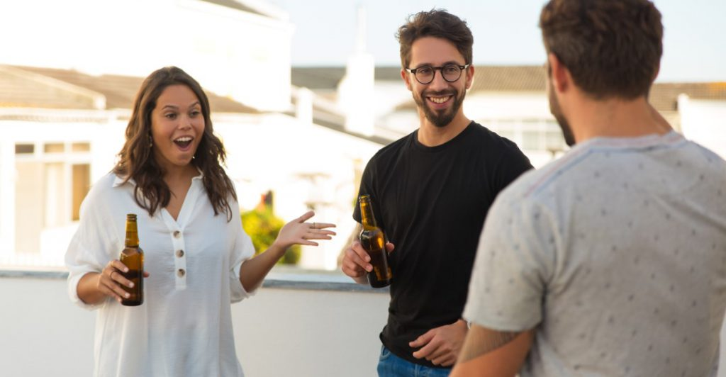 friends greeting each other and saying how are you on a balcony