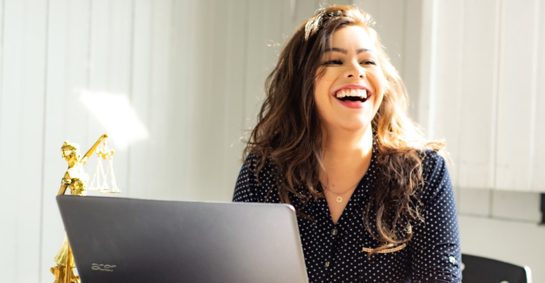 woman looking up on her laptop the best languages to learn for business