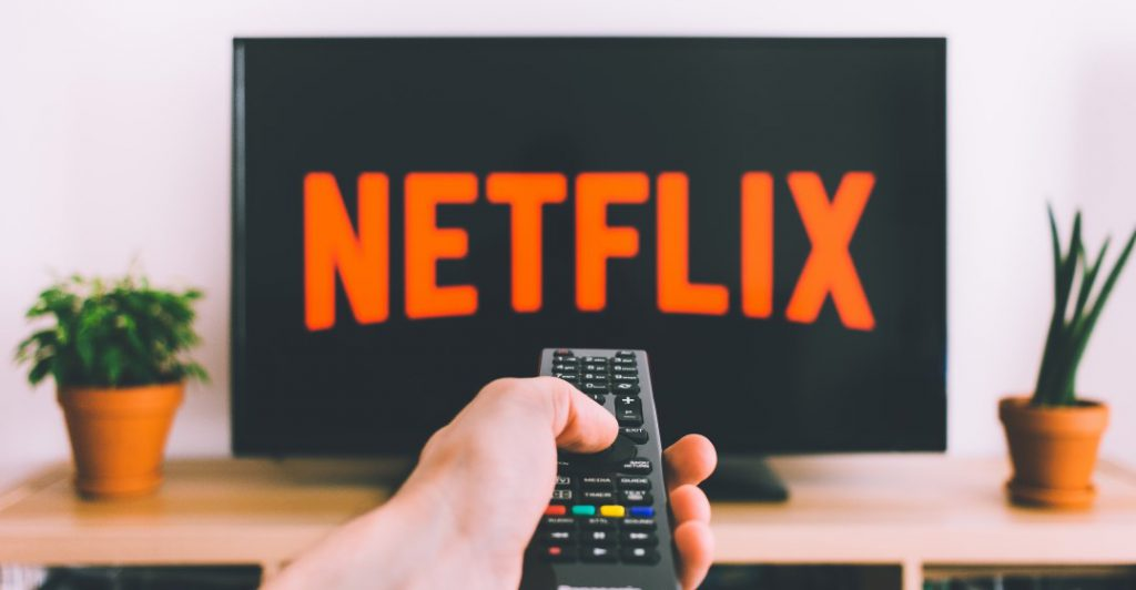 view of netflix screen with a hand holding a remote ready to watch spanish movies
