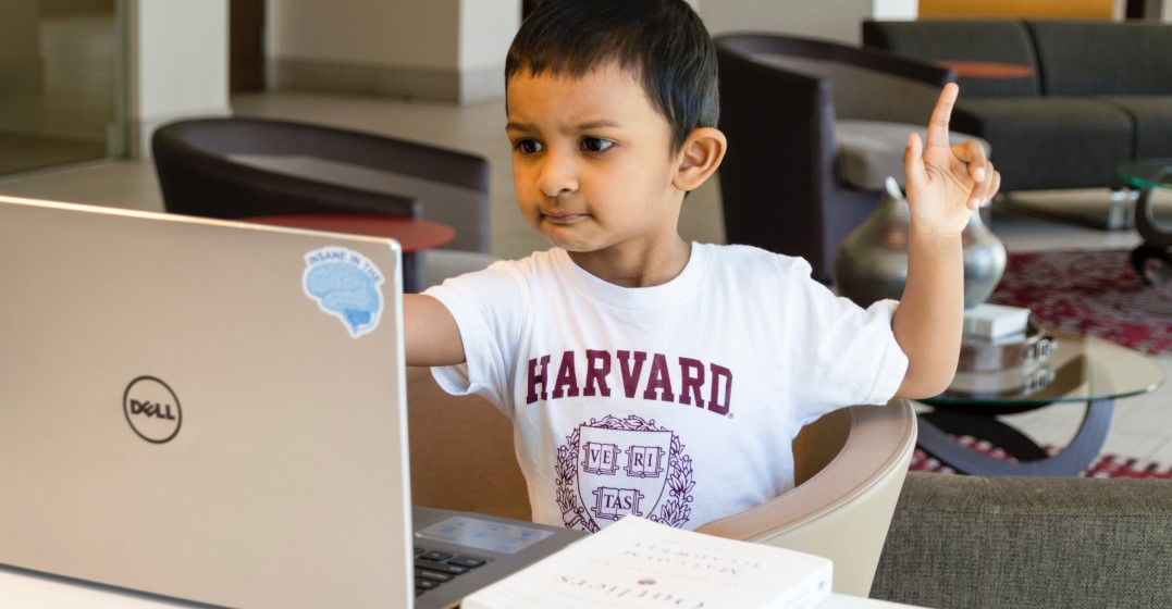 little boy learning a language from home on his laptop