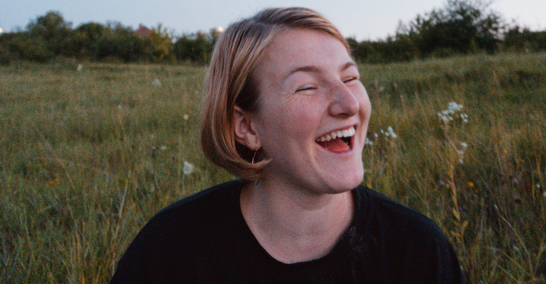 smiling woman sharing the best ways to learn a language as an adult