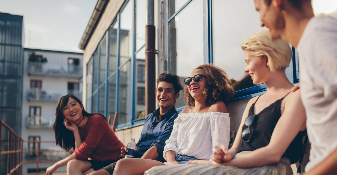 5 friends sitting on a bench on the rooftop of an industrial building, laughing and talking