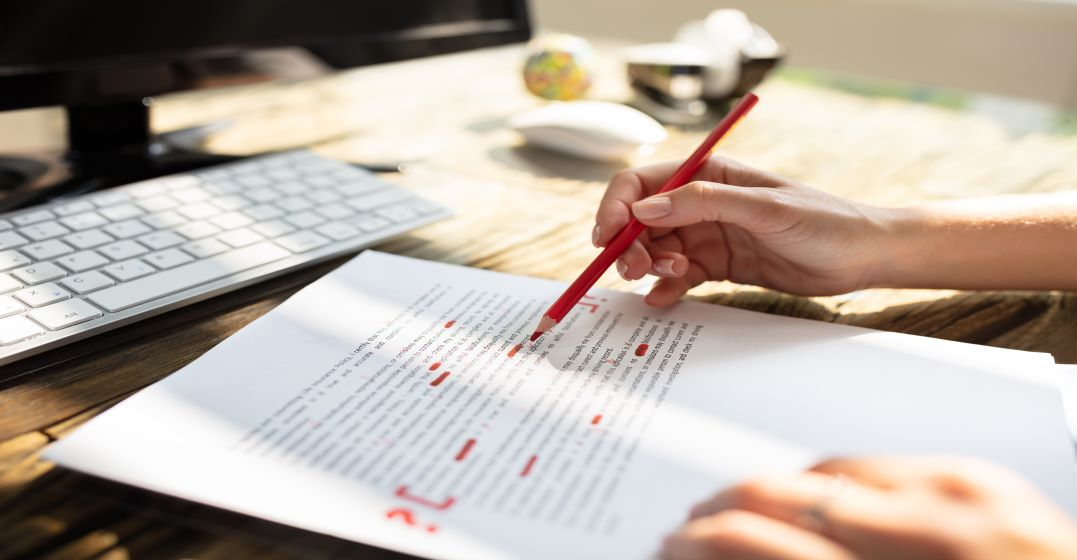 Text on paper being corrected with a red pencil