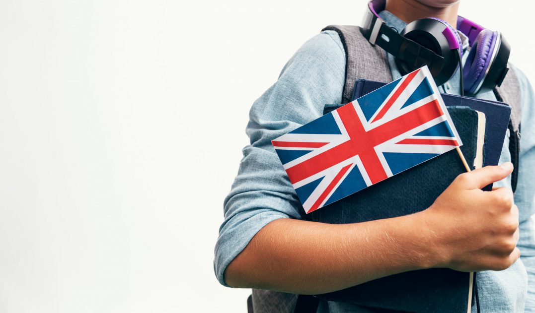 person holding books, headphones and a UK flag