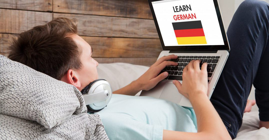 """Man laying on a couch with a laptop open, screen shows a German flag and the caption """"learn German"""""""